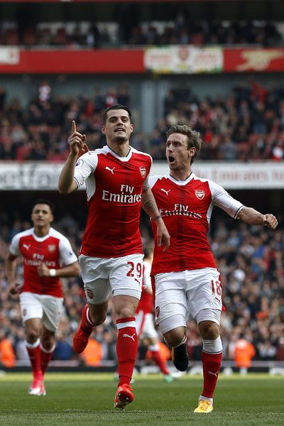 Arsenal's Swiss midfielder Granit Xhaka (C) celebrates after scoring the opening goal of the English Premier League football match between Arsenal and Manchester United at the Emirates Stadium in London on May 7, 2017.  / AFP PHOTO / IKIMAGES / Ian KINGTON / RESTRICTED TO EDITORIAL USE. No use with unauthorized audio, video, data, fixture lists, club/league logos or 'live' services. Online in-match use limited to 45 images, no video emulation. No use in betting, games or single…