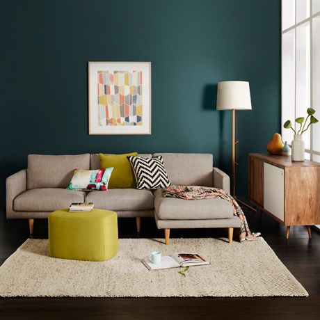 Mur bleu canard (foncé), canapé gris, pouf et coussin jaune/vert anis et graphique (chevrons noir