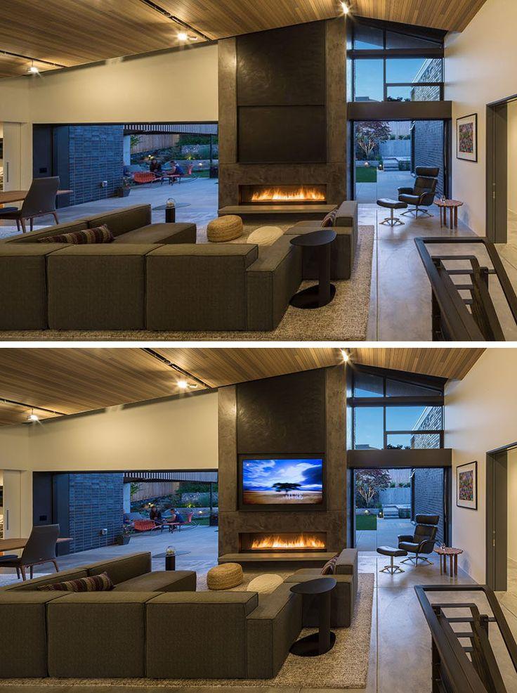 Dentro de esta casa moderna, hay puertas corredizas de vidrio de bolsillo que desaparecen en la pared para crear una experiencia de vida interior / exterior.  El salón tiene una lengua abovedado y techo de cedro ranura.  Sentado encima de la chimenea de gas es un panel motorizado que puede ser levantado para revelar la televisión.