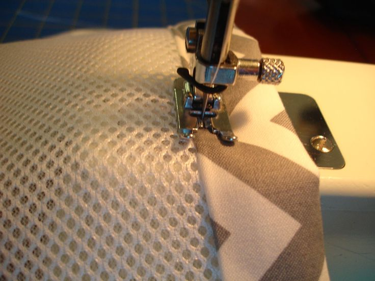 Using pre made mesh crib bumper, sew on coordinating fabric to match the bedding!