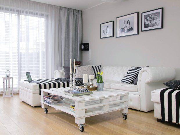 W salonie komfort zapewnia przepastna kanapa z pufami, które mogą służyć i jako dodatkowe siedziska, i jako podnóżki. Do tych mebli w klasycznym stylu Chesterfield zaskakująco dobrze pasuje stolik z palet. Na ścianie zalążek domowej galerii; na razie wiszą tylko trzy rodzinne fotografie, ale pani domu zapewnia, że z czasem będzie ich znacznie więcej.