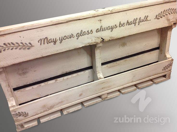 Cream coloured wine rack made from a wood pallet with notches at the bottom to hang wine glasses upside down. Hand lettered quote on top. Zubrin Design on Facebook