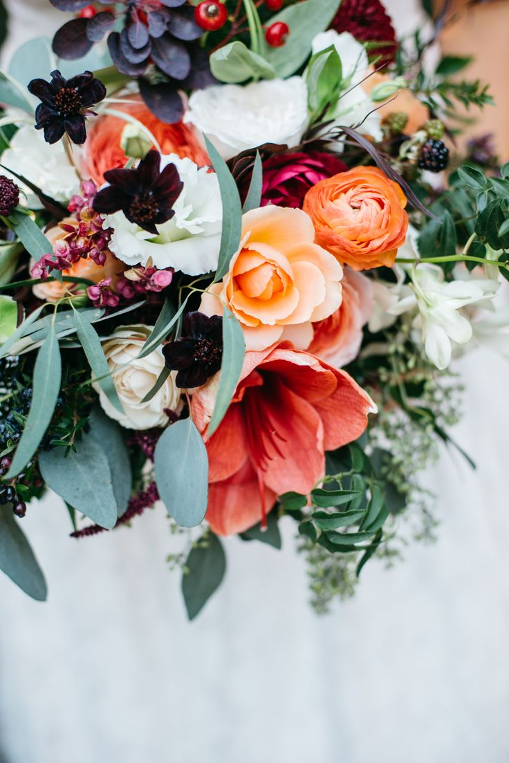 Fall bride and bridesmaid bouquet featuring coral amaryllis, ranunculus, garden roses, burgundy dahlia, smoke bush, eucaulyptus, dendrobium orchid and more. Flowers by Lily + Mint. www.lilyandmint.com. Photo by Studio 13 Designs.