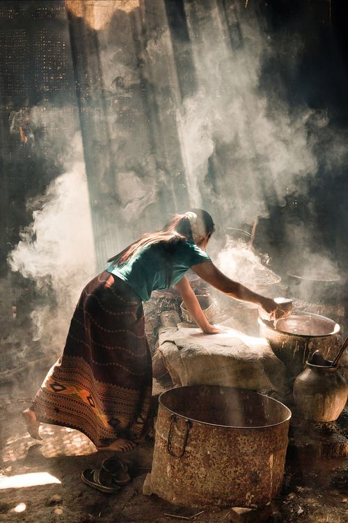 A woman is cooking rice crackers in a small hut at Inle Lake, Birma.  -- Your Shot. NATIONAL GEOGRAPHIC.