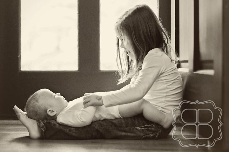 A big sister poses for photographer with baby