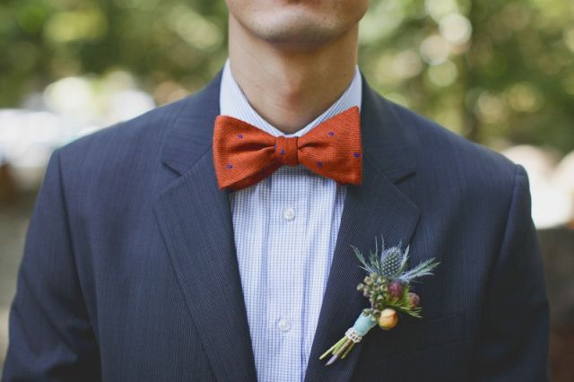 Persimmon hued polka dot bow tie paired with navy suit and ...