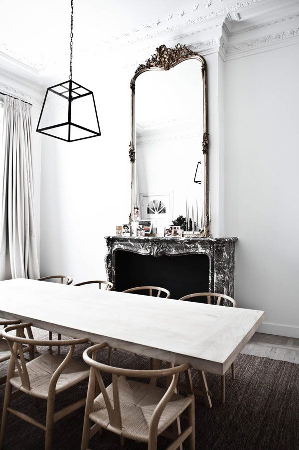 Love the juxtaposition of the contemporary dining table and the ornate mirror.