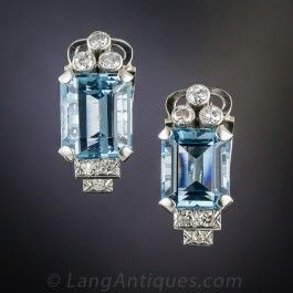 These gorgeous and glistening, bright sky blue aquamarine ear clips come to us from the mid-twentieth century with timeless, geometric Art Deco style at the forefront. The rich pastel blue gems are crowned with a sparkling trio of round diamonds and supported at the base with a classic diamond-set step motif. Chenier tubes adorn the side galleries of these cool blue ear baubles, hand-fabricated in gleaming and sturdy 14K white gold.
