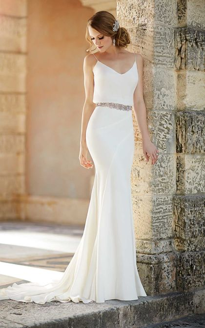 This '20s-inspired sheath wedding dress from the Martina Liana bridal gown collection features a silk Moroccan skirt paired with a sophisticated blouse top in Parisian silk chiffon. The attached belt is made from 3,000 encrusted Swarovski crystals.