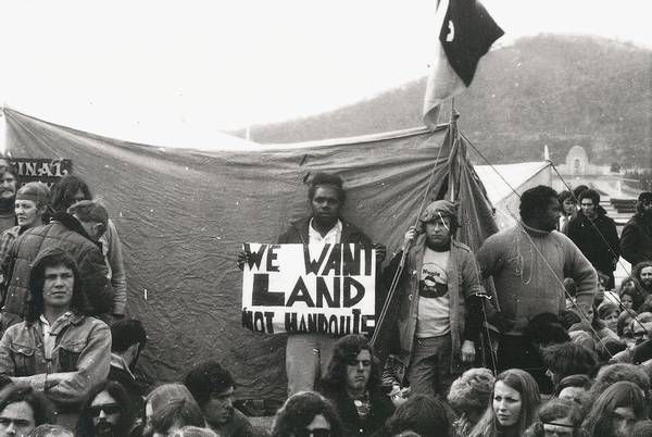 A large group of people, mostly sitting, in front of a tent. In the middle of the image Alan Sharpley stands holding a sign with black lettering on a white background: We want land rights not handouts. A flag flies from the front of the tent and the Australian War Memorial can be seen far in the background.