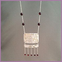 'Drops of Cherries' necklace: - light and alive, moving delicately with every step you take. A sterling silver two-panel necklace, decorated with fine line work reminiscent of cherry blossoms, continuing from one panel onto the next, and accented with a deep red garnets. Suspended from a 24 inch s-silver chain. Buy for $135.45 at http://mosadijewelry.com/collections/mosadi-necklaces/products/drops-of-cherries