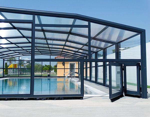 Au Portugal, pose d'un abri haut de piscine 5 angles avec porte accordéon.