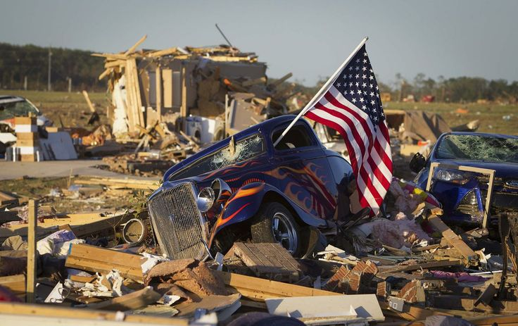 A U.S. flag sticks out the window of a damaged hot rod car in a suburban area after a tornado near Vilonia, Arkansas April 28, 2014. On a second day of ferocious storms that have claimed at least 19 lives in the southern United States, a tornado tore through the Mississippi town of Tupelo on Monday causing widespread destruction to homes and businesses.