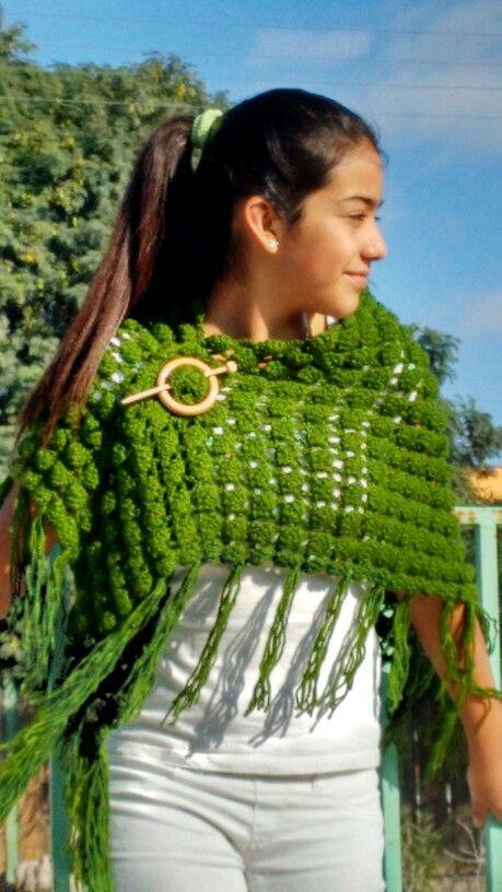 Shawl verde a crochet utilizado como capa con accesorio de madera.
