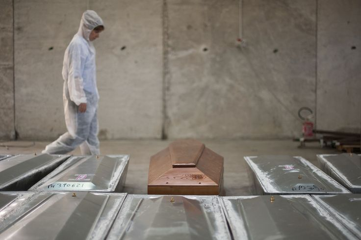 20161015 - A woman walks past lined up coffins at a NATO base in the Sicilian town of Mellili, Italy Cattaneo, a professor at the University of Milan, is leading a team of forensic pathologists who have volunteered to identify and catalog roughly 800 migrants who lost their lives in one of the worst tragedies in the Mediterranean migrant crisis. Her work is part of a unique, historic project expanding the field of humanitarian legal medicine and also part of a multi-million euro effort by…