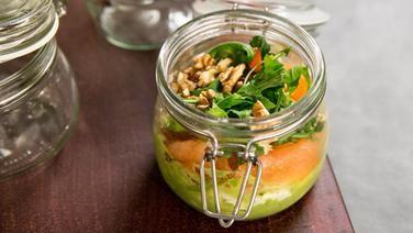 Ein Einmachglas mit Avocadopüree, Lachs, Rucola und Walnüssen