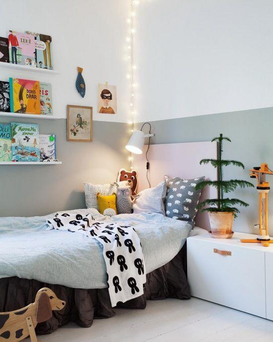 Ścianę w pokoju dziecięcym podzielono kolorystycznie bielą i szarością, mniej więcej do połowy wysokości. Meble oraz wiszące półki świetnie odwzorowują inspirację stylem skandynawskim.