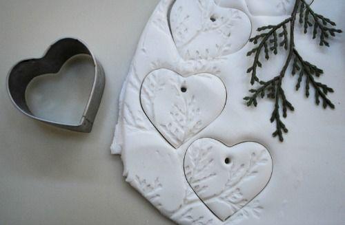 Nodig: zelfdrogende klei, een takje, een deegroller, een uitsteekvormpje, lint. Doen: rol de klei uit, druk het takje erin voor een mooie afdruk en steek de klei uit. Laten drogen en een lintje door het gaatje rijgen. Simpele kerst DIY's | Éénig Wonen