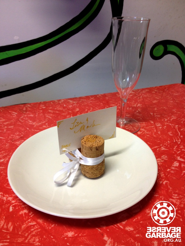 Reusing old corks >> Why not make some place card holders for your next dinner party or celebration using old cork? Two corks tied together with ribbon, with decorative cardboard used to display names. Everything in this photo is reuse and available at Reverse Garbage! Plastic champagne flute, corks, white plate, ribbon, decorative cardboard, pen to write names, table, canvas painting backdrop!