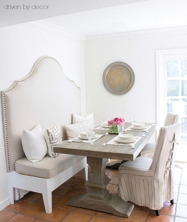 An upholstered banquette and pedestal table save space in a small eat-in area!