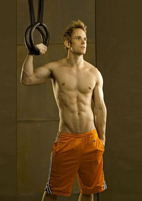 Lean shirtless hunk wearing long orange basketball shorts