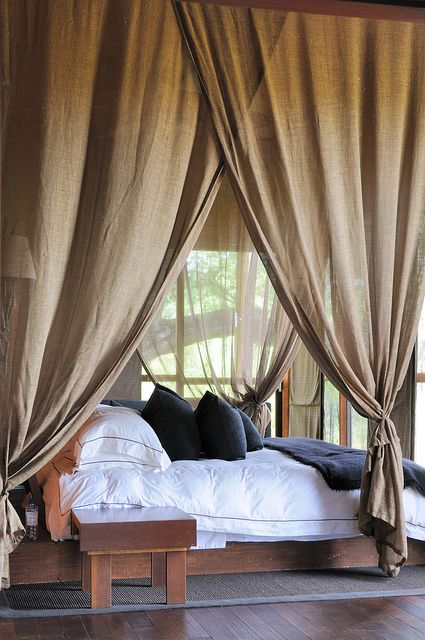 An amazing summer bedroom. Love the large mosquito net. The colour combination of whites, brown and navy work so well together.