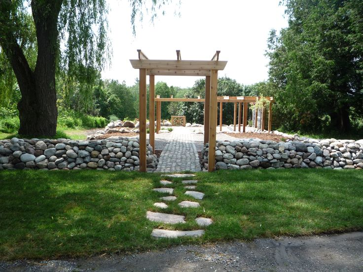 rustic garden, stone wall, granite flagstone pathways , granite edging, pergola,arch and old  shed.