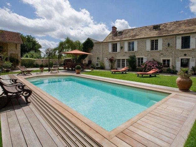 piscine install e devant une maison ancienne en pierre elle est entour e d 39 une terrasse en bois. Black Bedroom Furniture Sets. Home Design Ideas