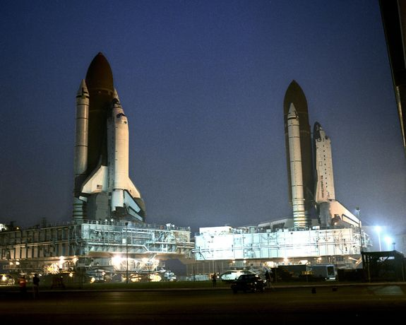 Atlantis, which was being prepared for its STS-38 mission, is seen parked in front of the Vehicle Assembly Building at NASA's Kennedy Space Center in Florida following its rollback from Launch Pad 39A for repairs to the orbiter's liquid hydrogen lines. Space shuttle Columbia (left), scheduled to launch on its STS-35 mission, is rolled past shuttle Atlantis on its way to Launch Pad 39A.
