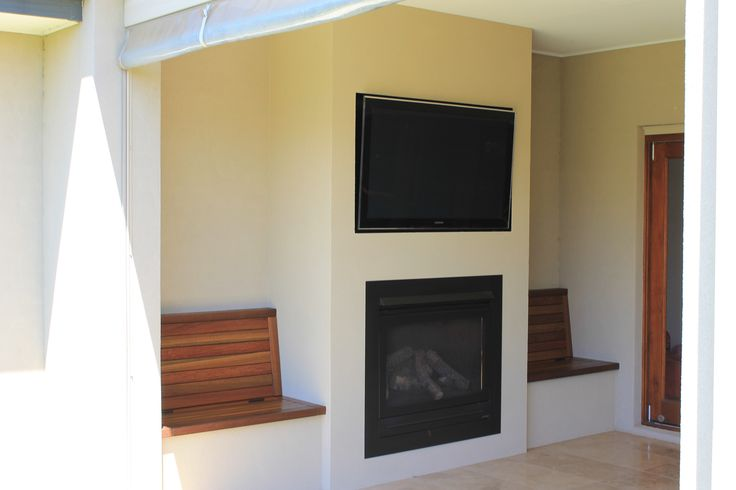 Outside Entertaining: Fire Place & TV wall with timber bench seating. Seats lift up for storage.
