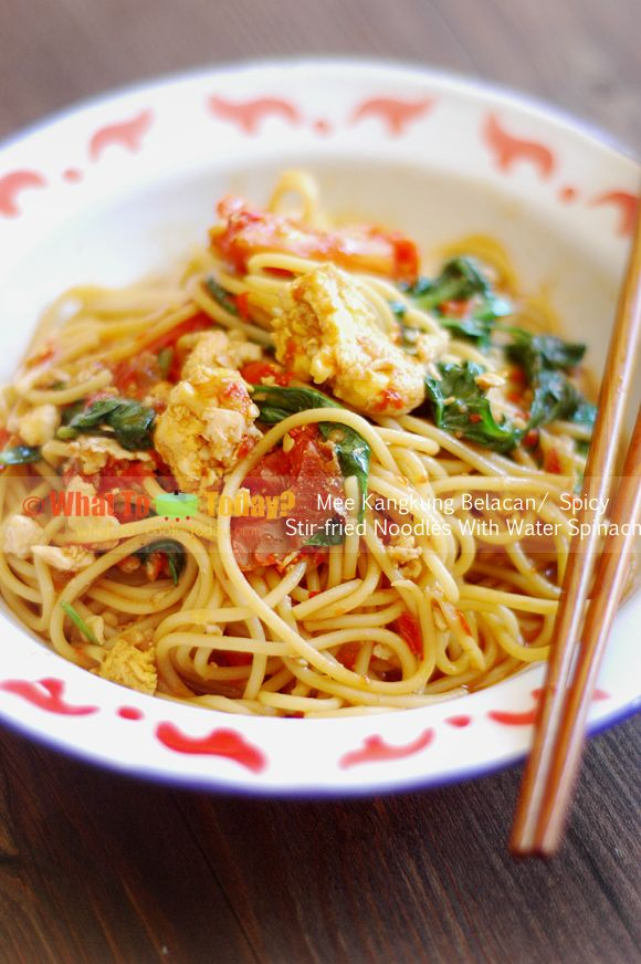 SPICY STIR-FRIED NOODLES WITH WATER SPINACH. Noodles are stir-fried with shrimp paste, chili sauce, eggs, shrimp, tomatoes, and water spinach or spinach.