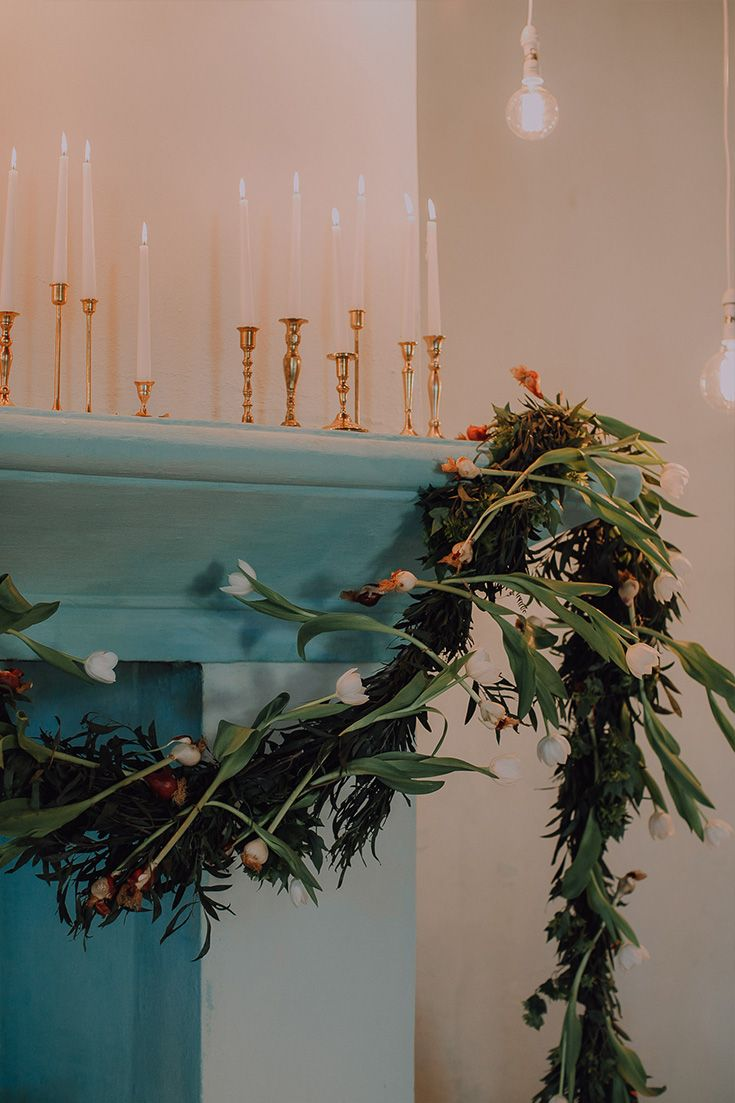 Beautiful Ceremony Decor at Hawksmoor House in Stellenbosch. This cozy chapel was decorated with lots of candles, naked bulbs and a tulip garland draped across the fireplace.
