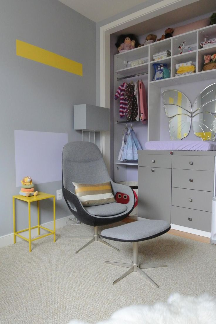 StudioHue designed this contemporary nursery to grow with the child, but for now a sitting area with a comfortable midcentury modern chair and ottoman have been placed in the room for parent and baby's needs. The soft gray color will allow bolder colors to be introduced with furnishings, knickknacks and other decorative touches, such as the yellow accent table and wall stripe and lilac pillow and wall square. Who says every little girl needs to be in the pink?