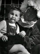 Huilend  kindje op schoot bij Zwarte Piet. Zonder plaats, [1952].