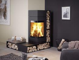 Modułowy kominek Elements z narożnym przeszkleniem. Jednolita zagięta szyba daje szeroki widok płomienia.