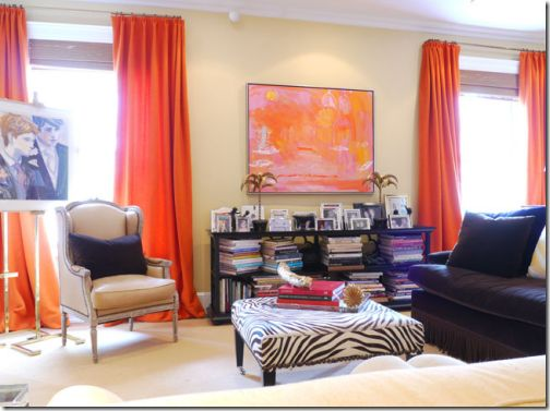 Bright orange curtains with pink & orange artwork in a room designed ...