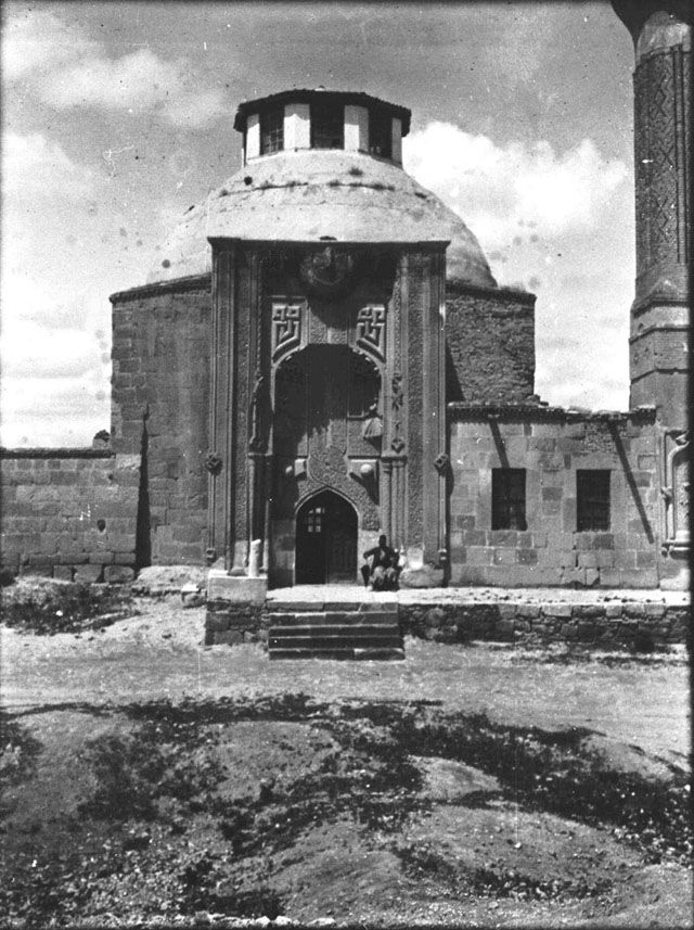 "Konya İnce Minareli Medrese-""Medrese with the Slender Minaret"" built by Emir Sahip Ata Fahrettin Ali. Elaborately carved entrance portal using Koranic script is example of baroque period in Seljuk architecture. Front view with Fattuh standing outside. Date taken: May 1905	 Photographer: Gertrude Bell Location: Konya - Turkey. Subject date: 1258"