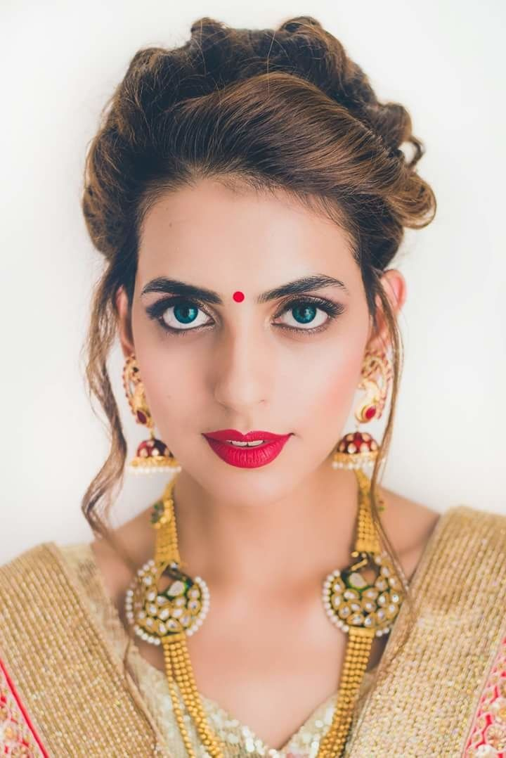 Hairstyles for Engagement - Swept Back Twisted Hairstyle with a Messy Bun with Red Bindi and Red Matte Lipstick | WedMeGood #wedmegood #bridalhairstyle #indianbride #indianwedding #red #gold