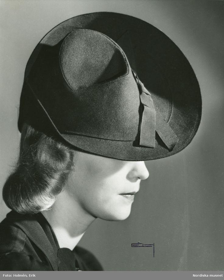 1939. Porträtt av kvinna i hatt med uppvikt brätte på sidan och ripsband, från Edward Molyneux. Foto: Erik Holmén