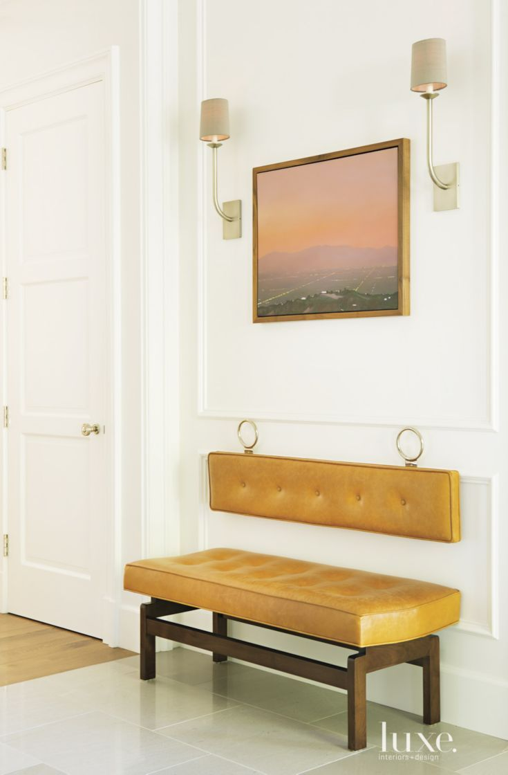 A custom midcentury-style leather bench from Orange stands in the foyer.