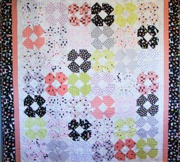 This quilt is definitely for the cat lover. Sweet kitties adorn the fabric and the colours are so pretty in coral, black, chartreuse, grey and white. The quilting features a cat motif as well.