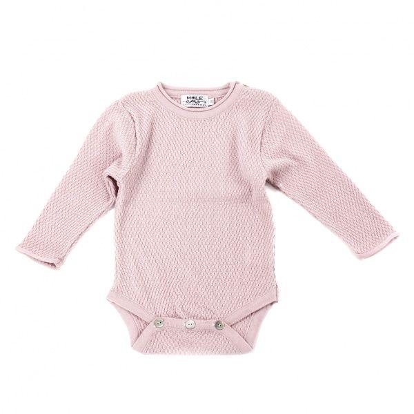 Perlestrikket babybody som er en litt tykkere enn vanlig body og kan fint brukes som et mellomplagg.  Finstrikket i merinoull som kan vaskes i maskin på ullprogram og tørkes lett på svak varme i tørketrommel.  Fås i fargene lyseblå, rosa, brun, lysebru