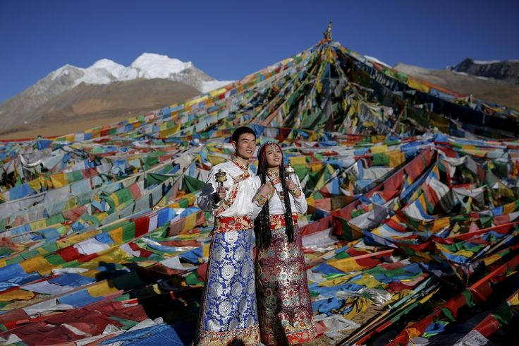In Tibet, on the eve of the wedding day, the groom brings his bride a wedding dress and accessories. The outfit can include a headdress, silver coins for hair decoration, and a small metal Buddha amulet.