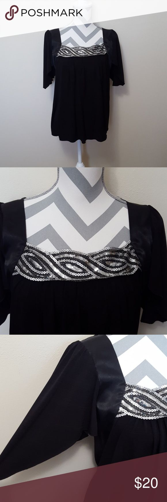 XOXO Embellished Black Sequin Dress Blouse Price Reduced! XOXO brand in a size Medium but can fit a Large. The bottom is very flowy and could even be used as a maternity top. The neckline is embellished with bling sequins and also has batwing sleeves. It would be the perfect blouse for a date night or a night on the town. Body: 95% Polyester and 5% Spandex. Contrast: 100% Polyester.  Smoke free home and fast shipping. I do offer bundles deals as well. Thank you for checking out my closet…