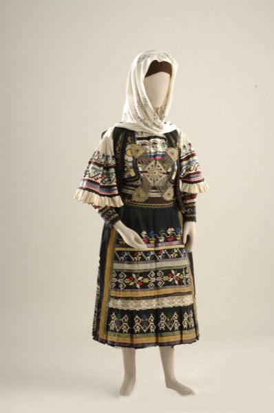 Sarakatsani bridal costume from Attica 19th-20th c. The main characteristic is the similarity of its features with those of the corresponding men's costume - the embroidery on the sleeves of the chemise, the decoration on the plisedoti (pleated) skirt and the embroidery on the apron. A distinctive accessory of this costume is the tsaprazi or cross, a large chain ornament worn on the chest [http://attica.unipi.gr/culture/article.php?article_id=110&lang=en]