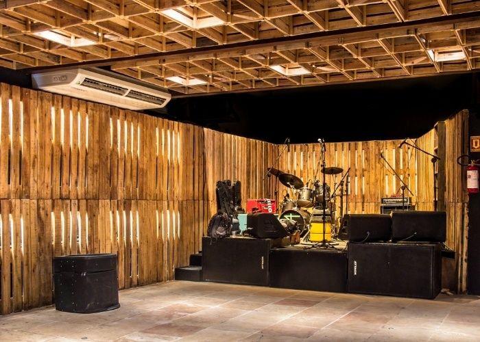 """O escritório A&P Arquitetura e Urbanismo usou materiais reaproveitados para revestir uma casa de shows em Salvador (BA). A fachada e as paredes internas receberam pallets de madeira e, o forro, foi ocupado por caixas de fruta. O projeto foi um dos premiados na categoria """"Casas Noturnas"""" do Melhor da Arquitetura 2013"""