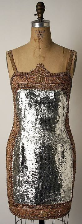 vintage 1920s flapper style with silver lame overlay…By 1926 skirts were at their shortest in the Twenties decade and showed the knee until 1928. The whole leg as far as the kneecap was revealed this was the height of flapper fashion.