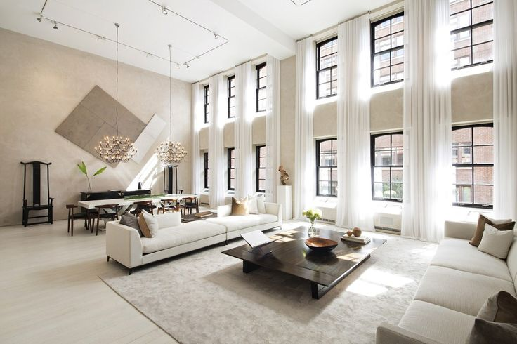 """This apartment occupies a generous 6,471 square foot floor plan centered on a great room with a double-height ceiling, its lovely neutral interior flooded with light from windows that span the 17'5"""" walls. The current design maintains the characteristic industrial details from the property's former life, setting the stage for a glamorous modern interior in line with today's minimalist tastes. Track lighting, spectacular chandeliers, and eye-catching artwork offer abundant interior decor…"""