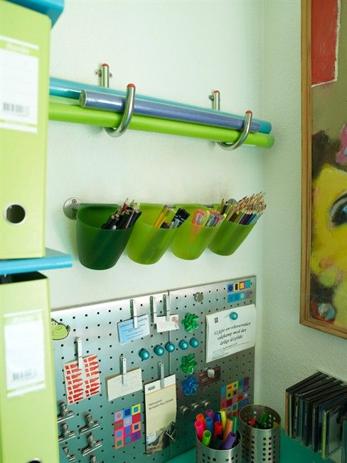 store pens and colour pencils in plastic cups hooked to a towel rod. Add a magnetic board for notes. And towel hooks to hold up coloured paper or bristol boards