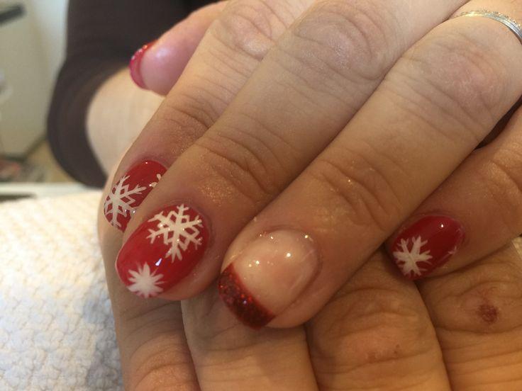Nail art noel. Flocon de neige. Ongles en gel. French de couleur rouge paillettes.